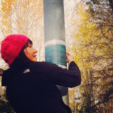 The writer tapes her broadside to a metal lamppost in Anchorage with yellow aspen in the background.