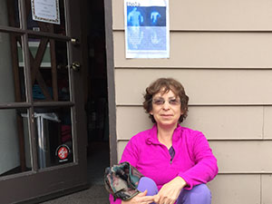 Poet sitting against wall with broadside taped above her.