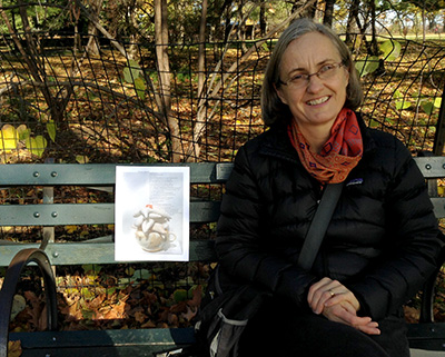 Artist smiling on right sitting on bench next to broadside taped on it on left.