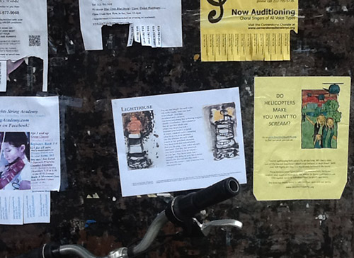 Broadside on wall next to other posters with bike handles showing right below.
