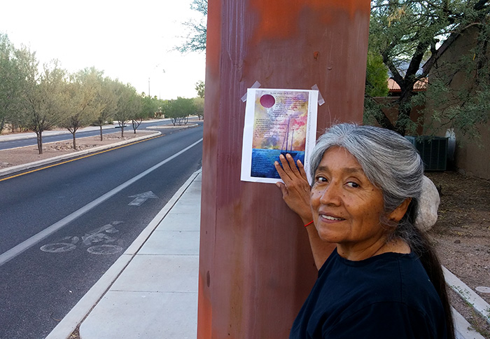 Poet smiling and looking over shoulder at camera, with broadside taped on structure on street behind.