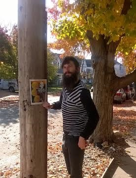 Poet posing next to broadside on pole with tree behind him.