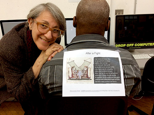 Artist smiling at camera, leaning on colleague with back to us, staring at computer screen, with a broadside taped on his back.