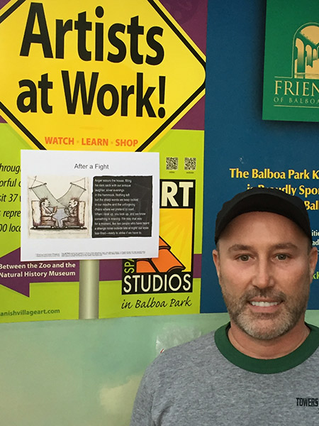 Poet standing in front of several posters with broadside, on left, taped onto posters behind him.