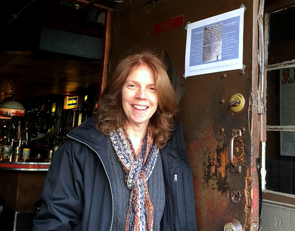 Translator, smiling, leaning against doorway with broadside taped at top.