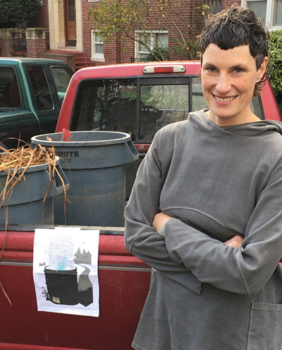 Artist, smiling, next to broadside taped on back of red truck filled with some trash cans..
