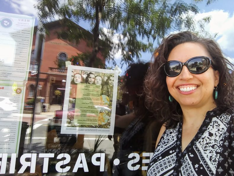 Poet, smiling next to broadsided on left taped onto window.