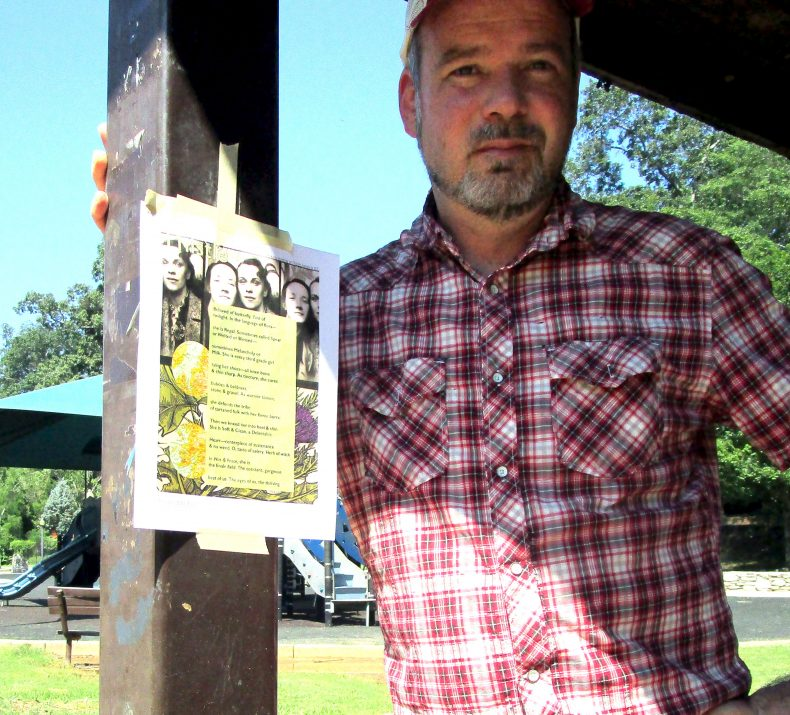 Artist, standing and looking into distance with broadsided taped on pole on left.