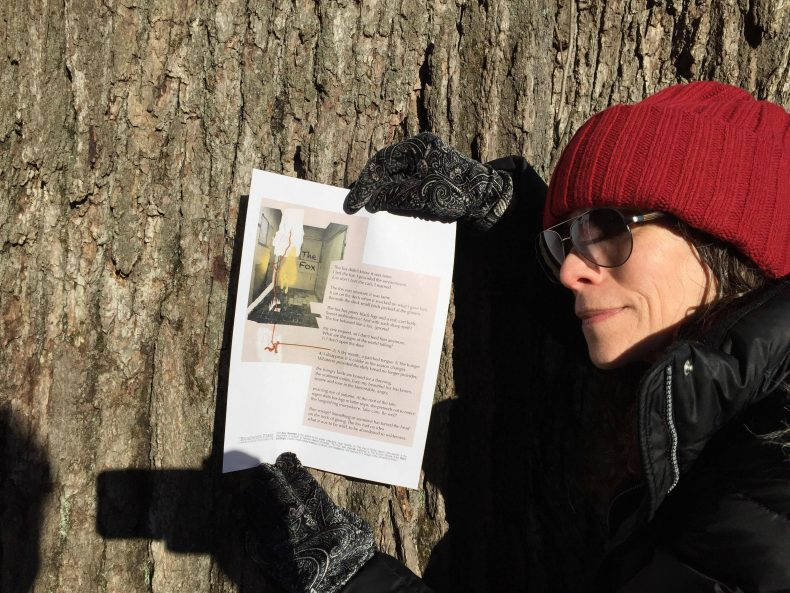 Artist in hat and sunglasses at profile holding broadside against tree.