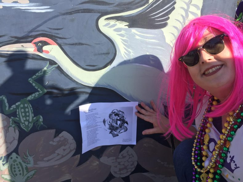 The poet in pink hair stands right of her broadside posted on a mural of a flying crane.