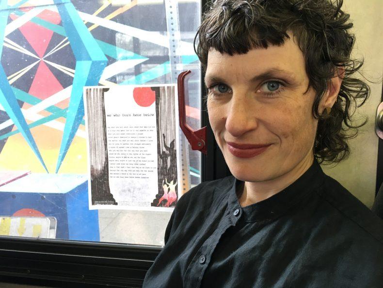 Artist Sarah Van Sanden stands right of her broadside posted on a colorful mural.