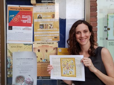 Poet, on right, smiling and holding up broadside in front of bulletin board with multiple posters.