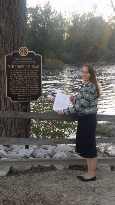 """Poet holding up broadside next to sign of """"Thiensville Dam"""" with river in background."""