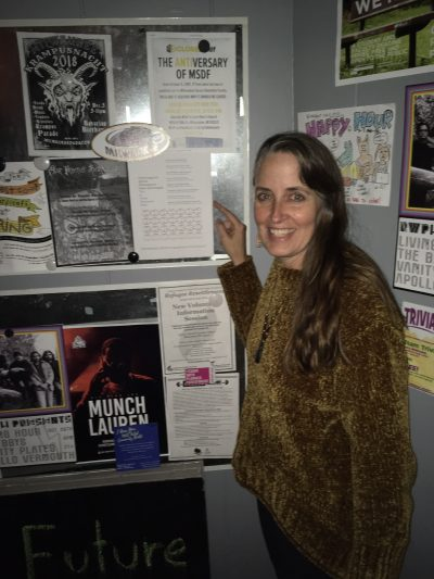 Poet with broadside on bulletin board covered with posters.