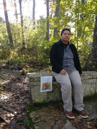 Full length portrait of artist in forest, sitting on stone bench with broadside on side of bench.