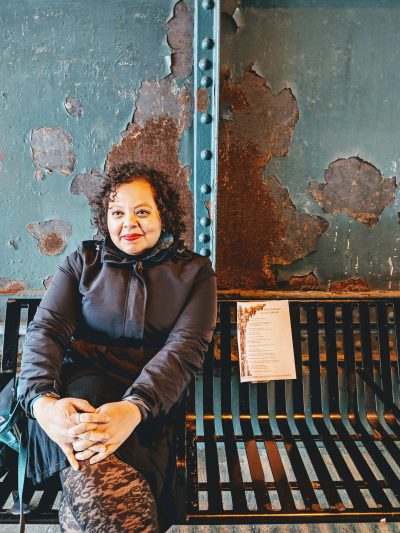 Poet smiling sitting on bench with rusty and peeling dark green-grey metal walls behind.