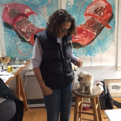 Artist peering down on tiny dog on stool in studio with pictures in background.