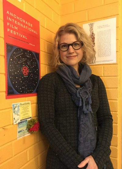 Three quarters shot of artist smiling in corner of yellow brick wall with broadside behind her on right side.