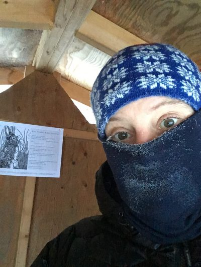 Artist Sara Tabbert, covered nose-down with a muffler, stands in her rental cabin with her broadside posted on a wood panel in the back.