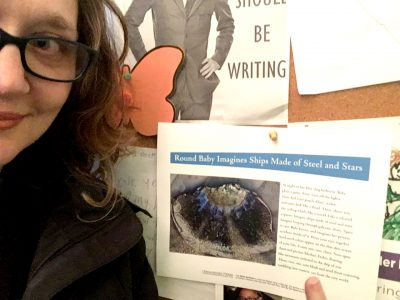 Poet Sheila Squillante, showing half of her face, stands left of her broadside posted on a notice board along with other flyers.