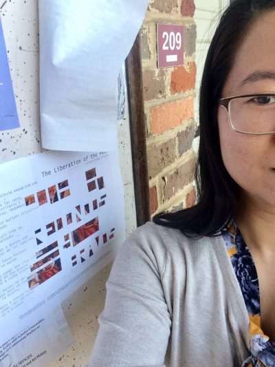 Artist Millian Giang Pham, showing half of her face, stands in front of her broadside posted on a notice board.