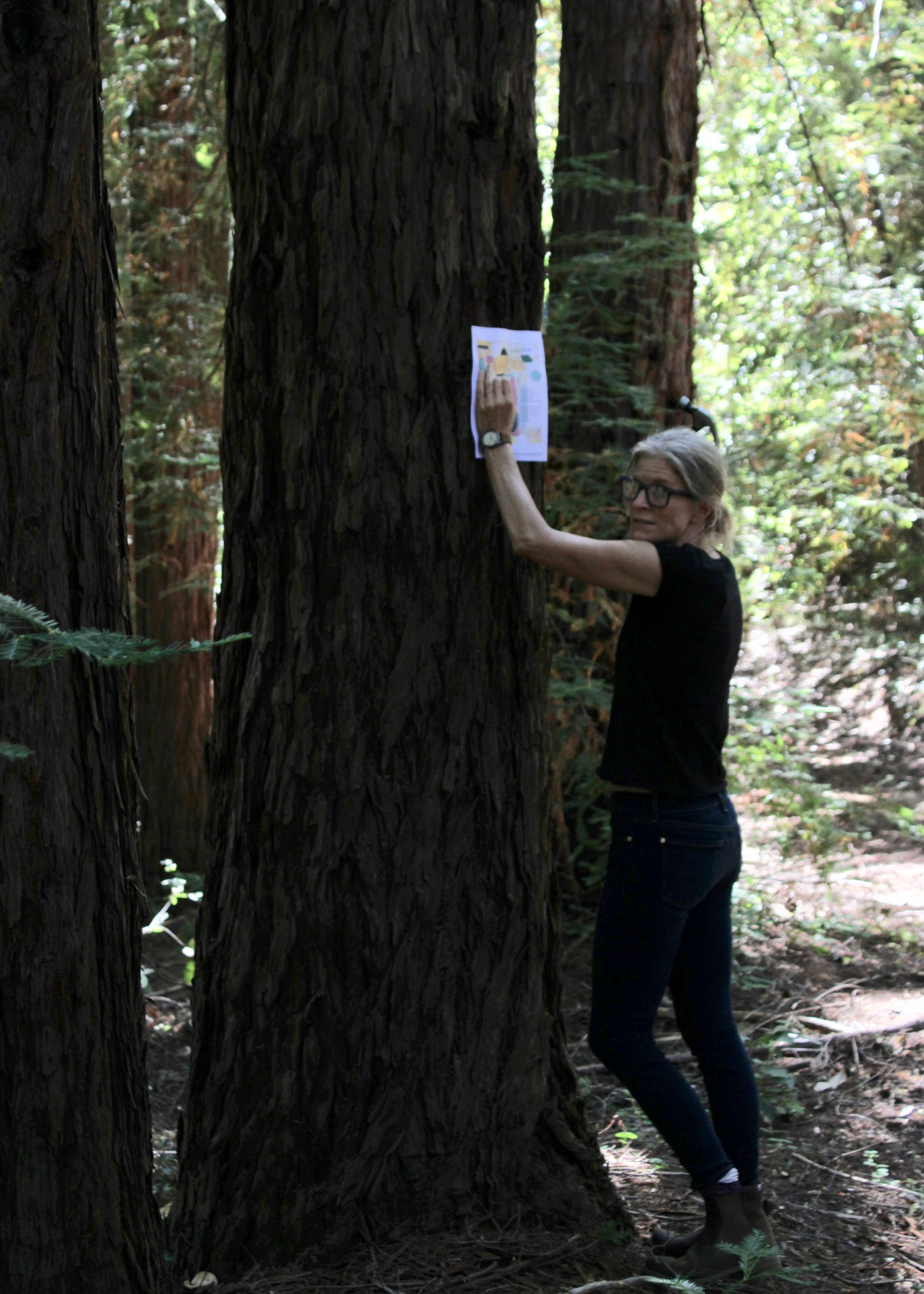 Full shot of poet standing next to large tree pressing Broadside to tree.