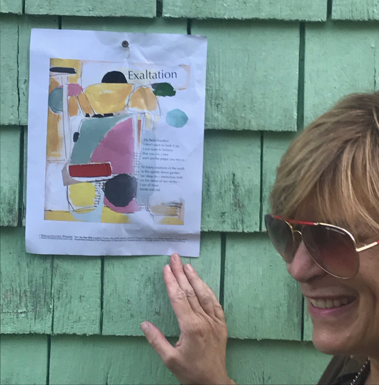 Three quarters profile of artist smiling on right with Broadside behind on green wall.