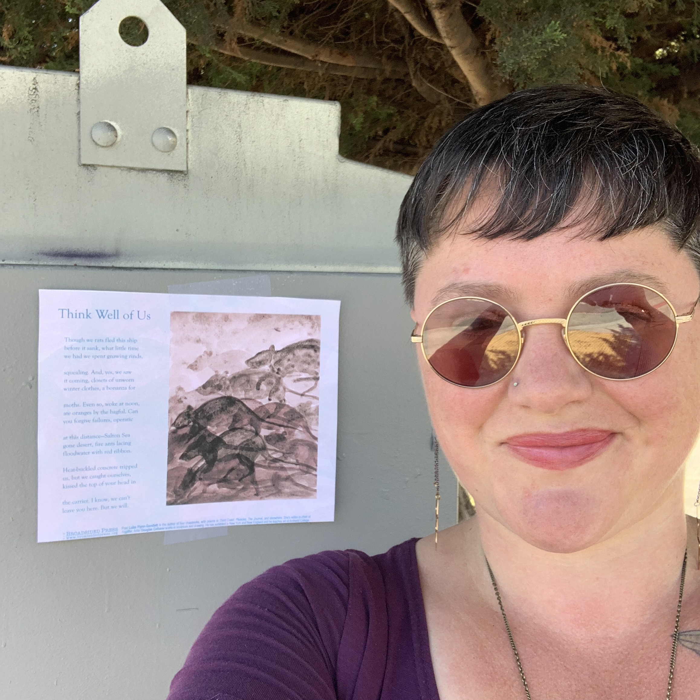 Close up of smiling poet standing in front of Broadside on the left.