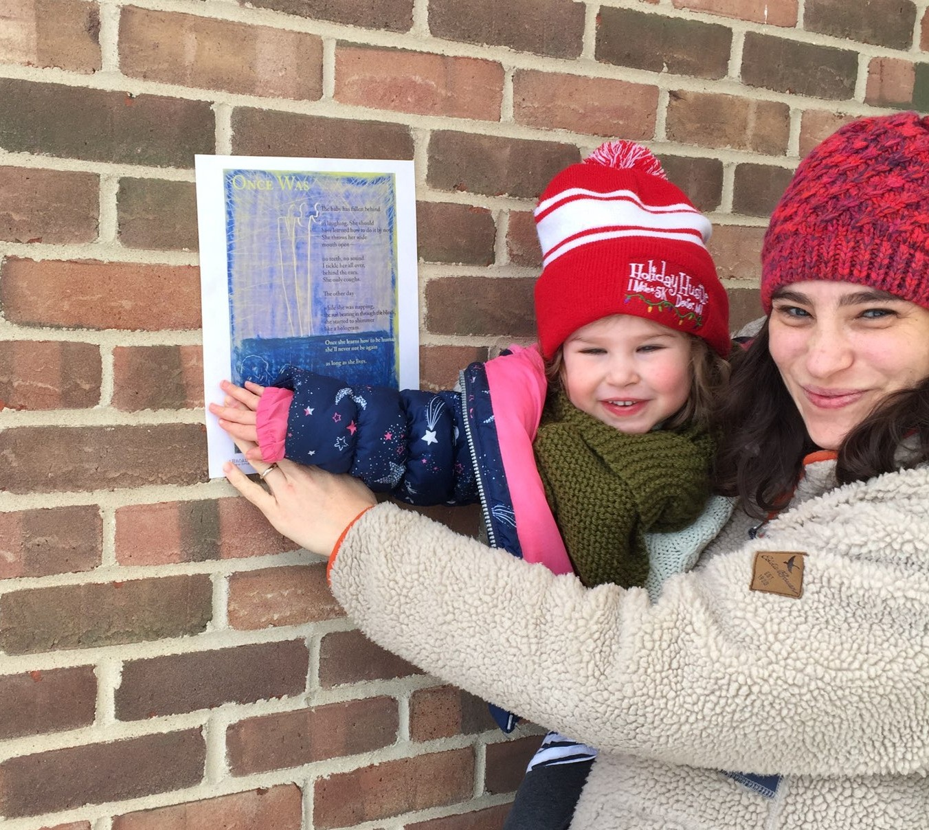 Poet Adina Schoem and her child, both in red hats, stand right of her broadside posted against a brick wall.