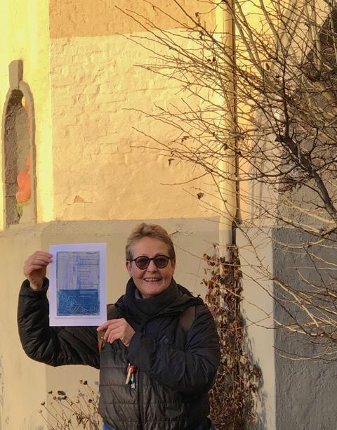 Artist Åse Margrethe Hansen holds her broadside next to her face in front of a building and tree drenched in winter sun.