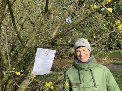 The artist stands beside a scrawny tree upon which the broadside has been affixed.