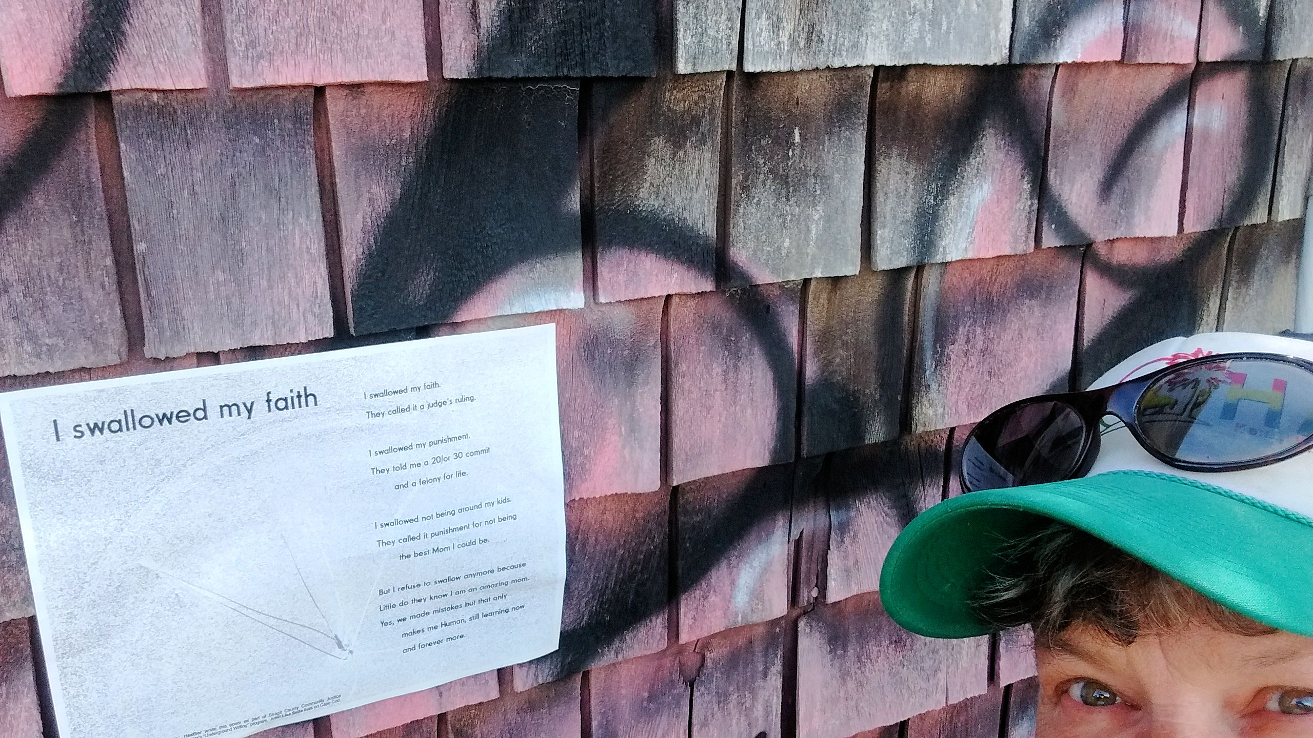 Lisa Sette stands right of her broadside pasted on a pink, graffitied wall.