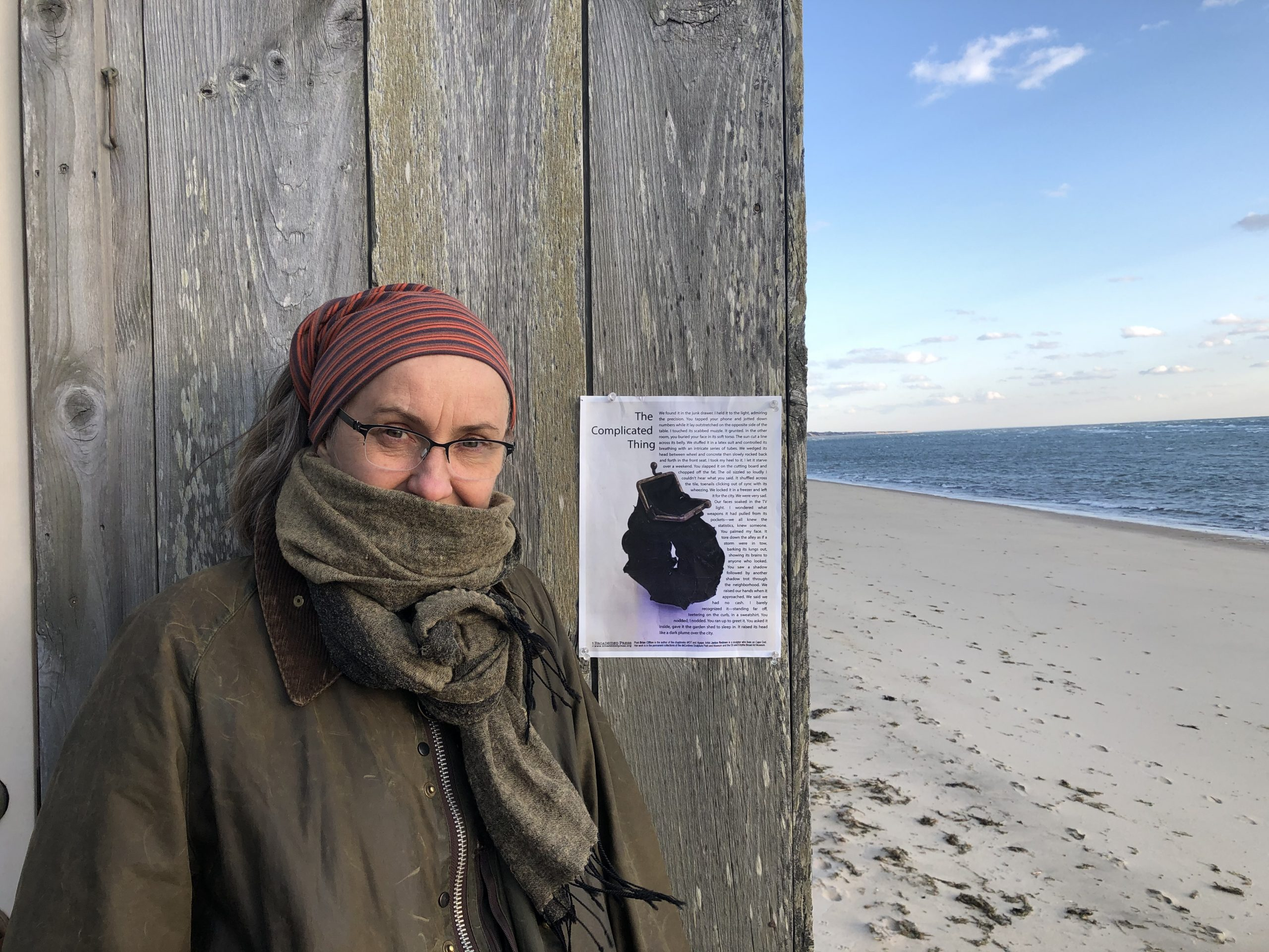 the artist standing in a hat and scarf in front of a wooden wall by the sea.  Her broadside is on the wall.
