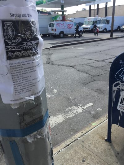 Broadside taped to a utility pole in front of a lot parked with graffitied vans.