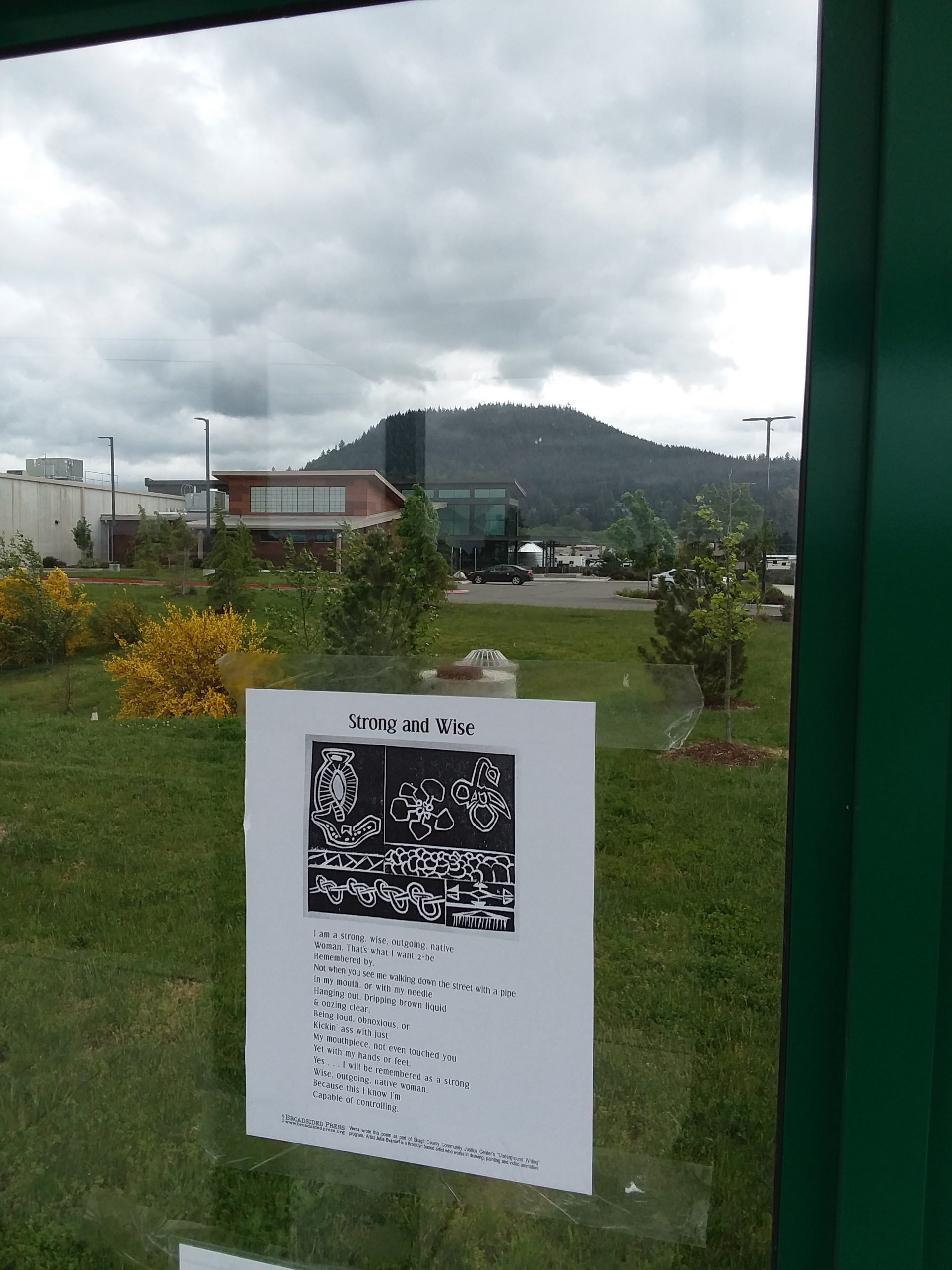 The broadside posted on a glass window beyond which stands the correctional facility where the poem was written.