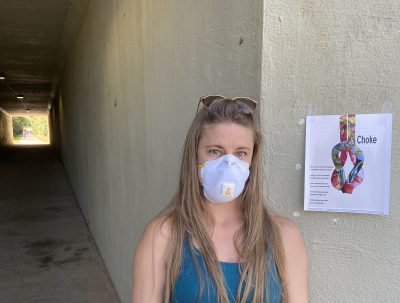 Wearing a face mask, standing in front of a concrete wall upon which her broadside is taped.