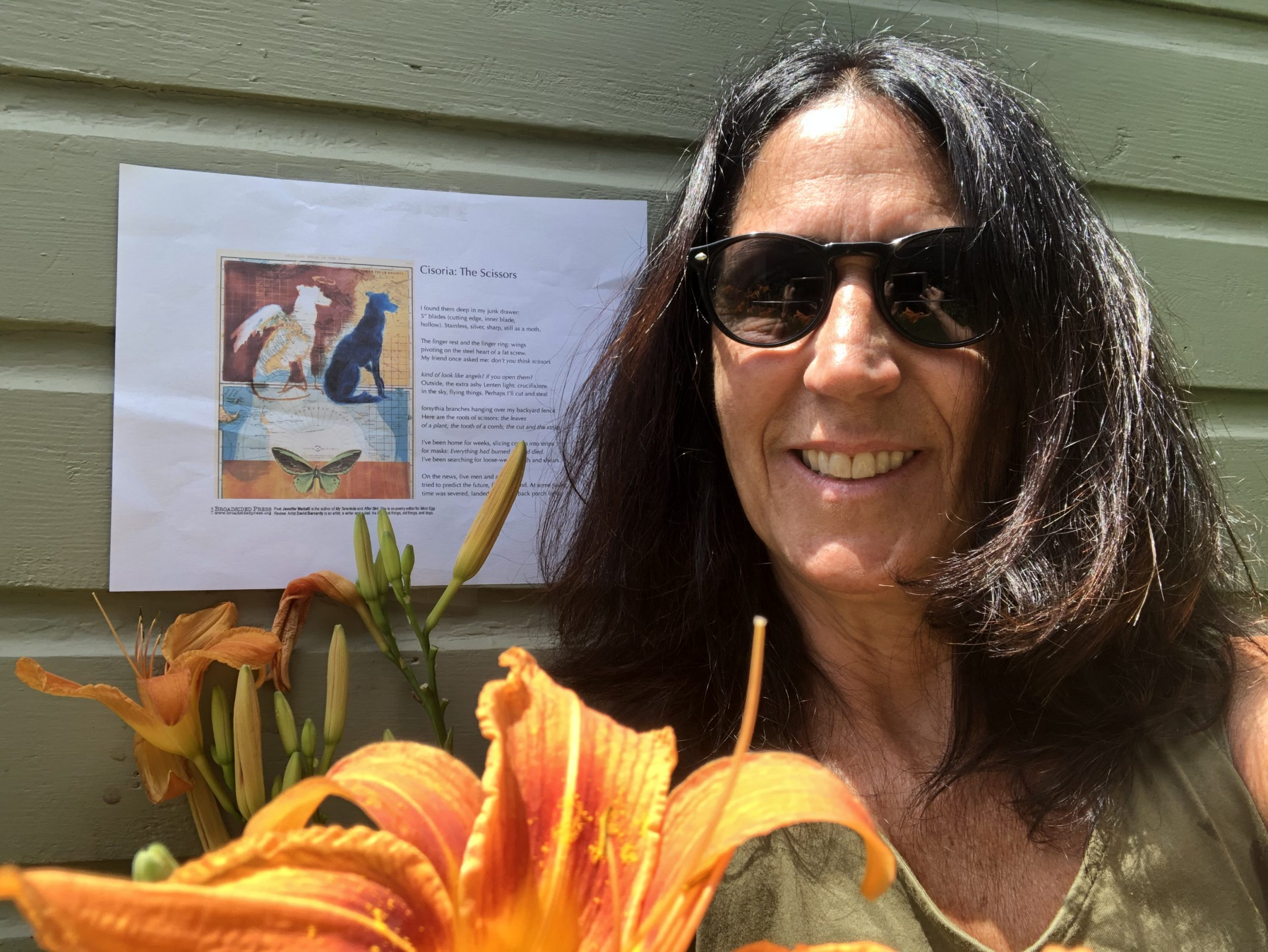 Close up of smiling poet in front of Broadside with flowers in bottom edges of picture.