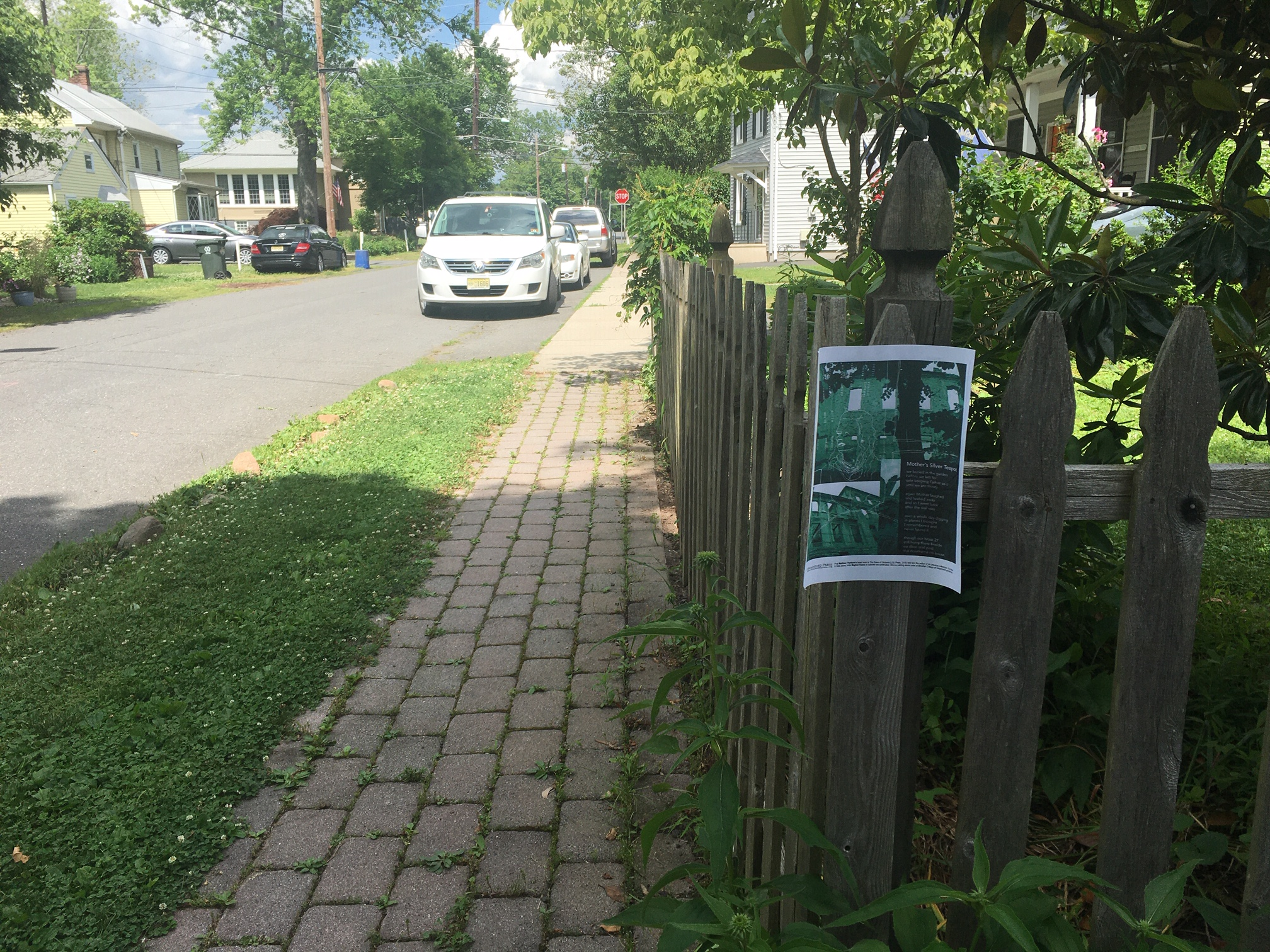 Broadside on corner of fence on sidewalk stretching forward with cars towards the end.