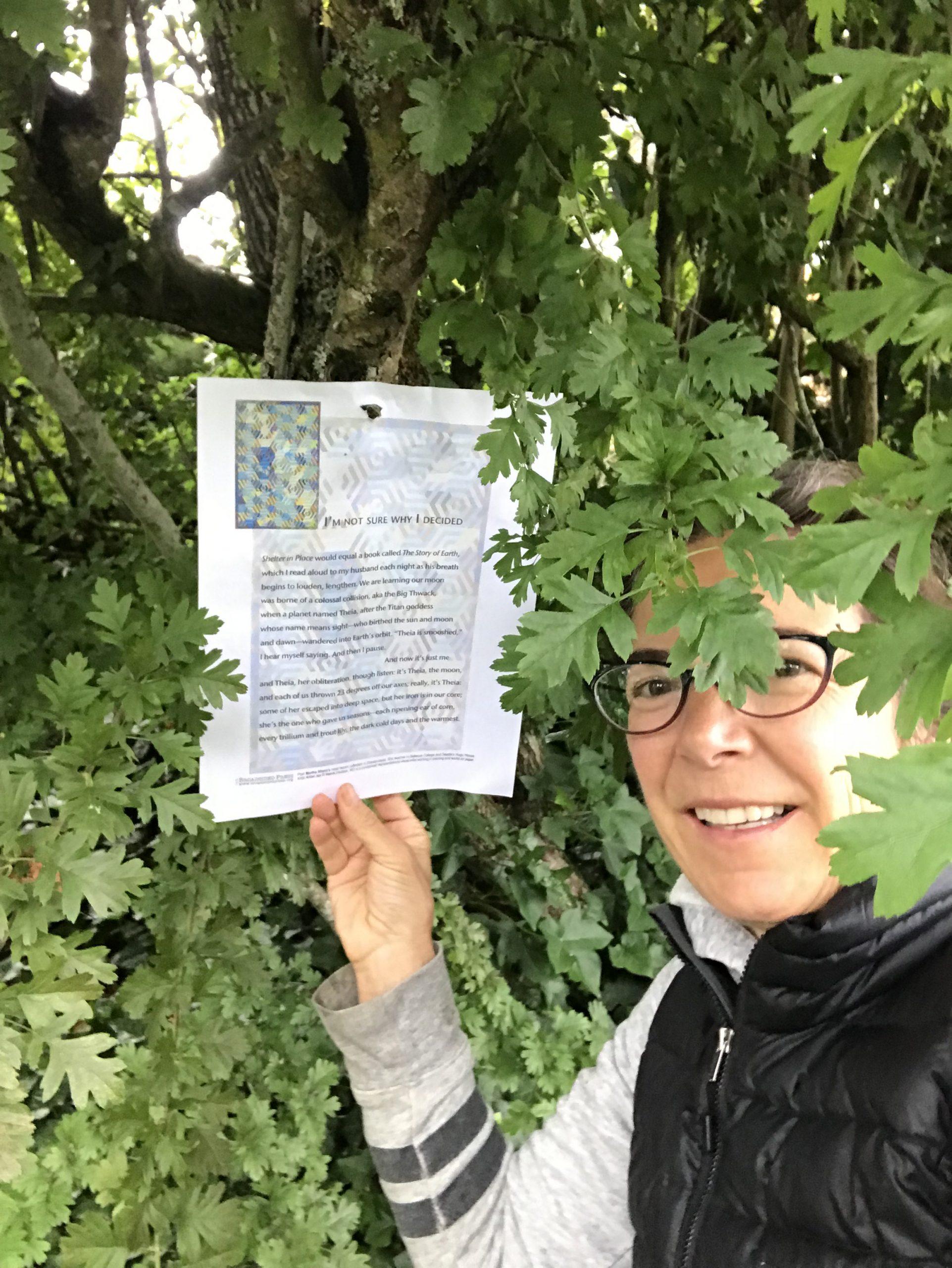 Martha Silano under oak leaves next to her broadside.