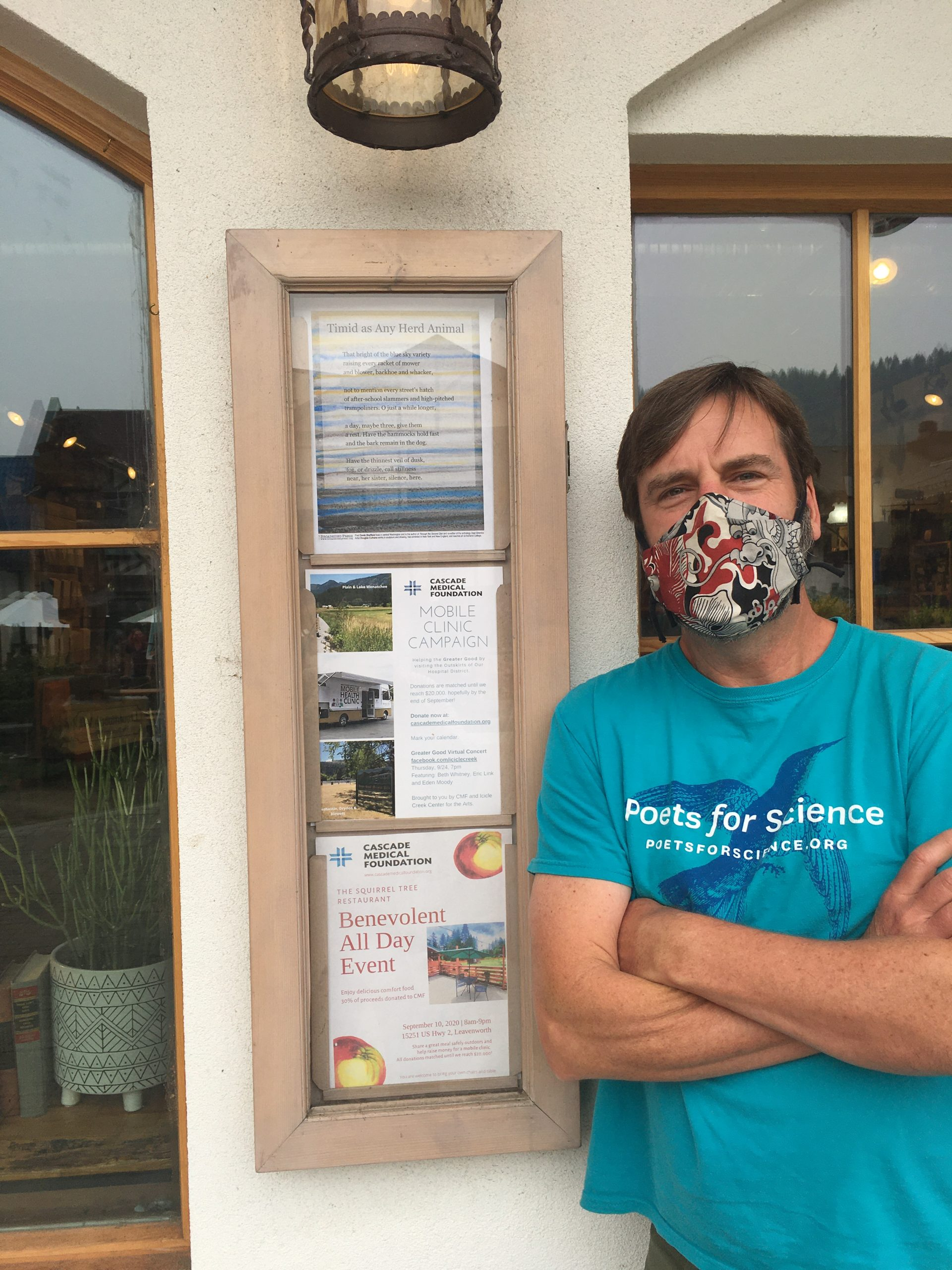 Poet's friend in blue shirt posing next to the Broadside which is in the top space in a wooden frame on a white wall.