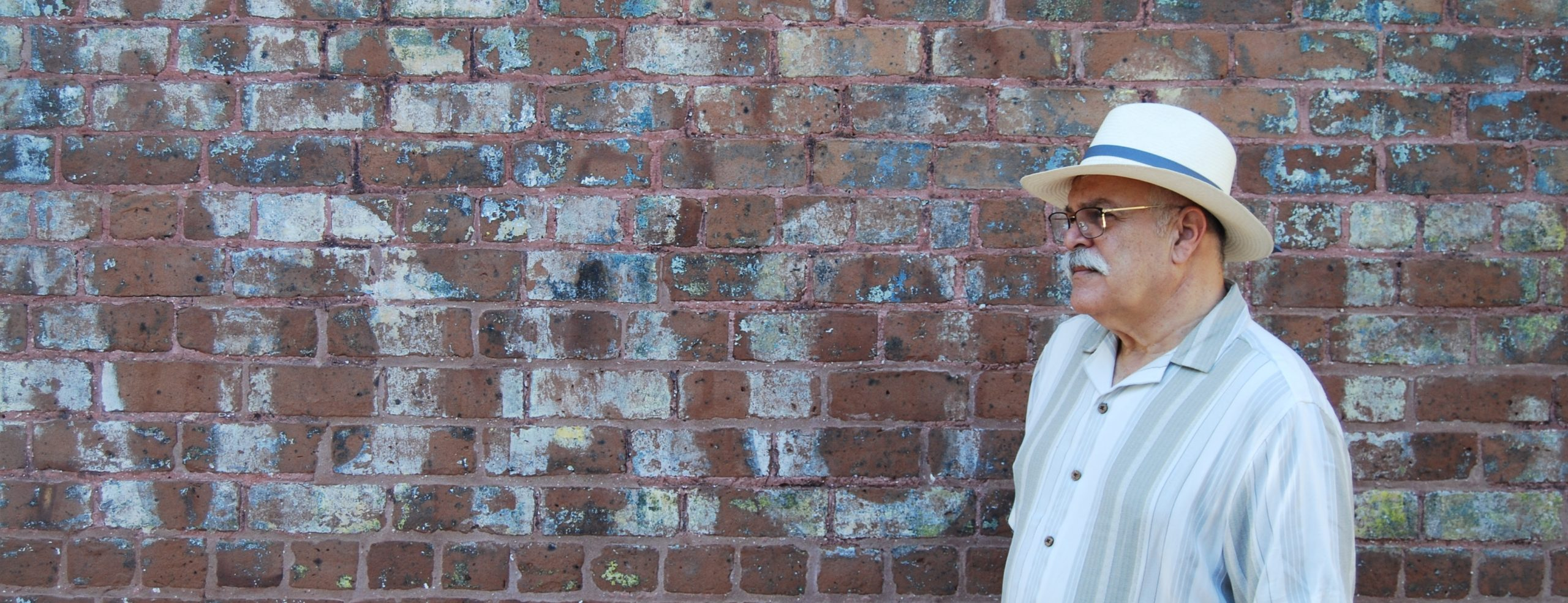 """Translator in white fedora on far right, behind a brick wall with painted letters including """"A-D-A-C."""""""