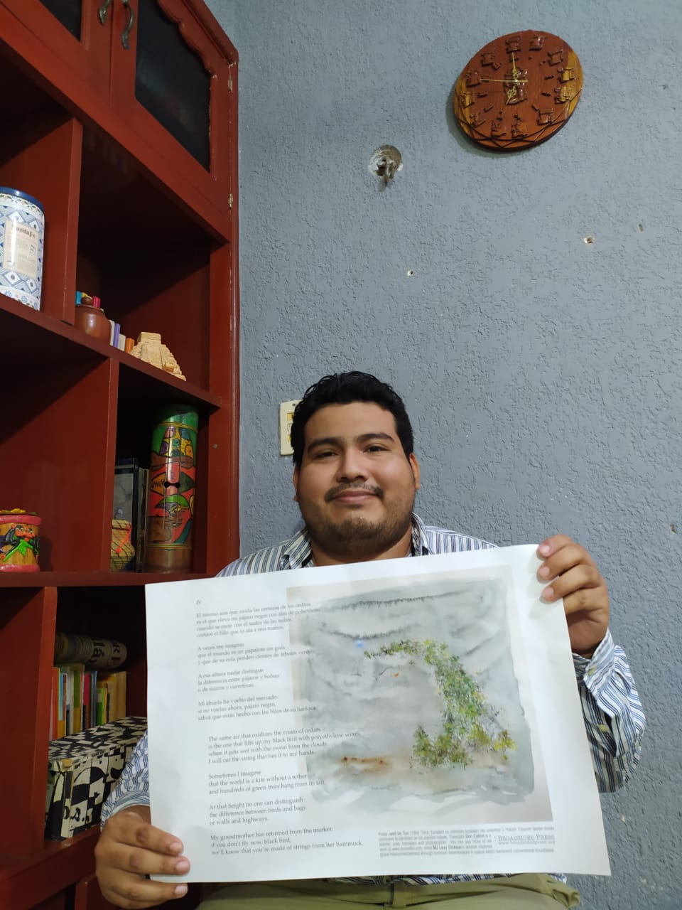 Poet holding up larger print out of Broadside right below his head, sitting next to red shelf and smiling.