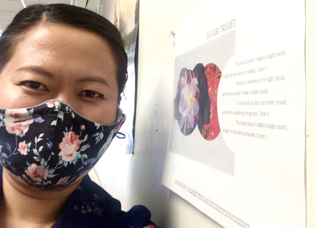 Artist with flower mask poses on left of Broadside taped to wall running perpendicular to her.