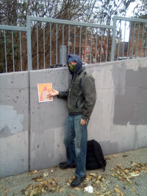 The poet James Ellenberger stands right of his broadside posted against a gray wall.