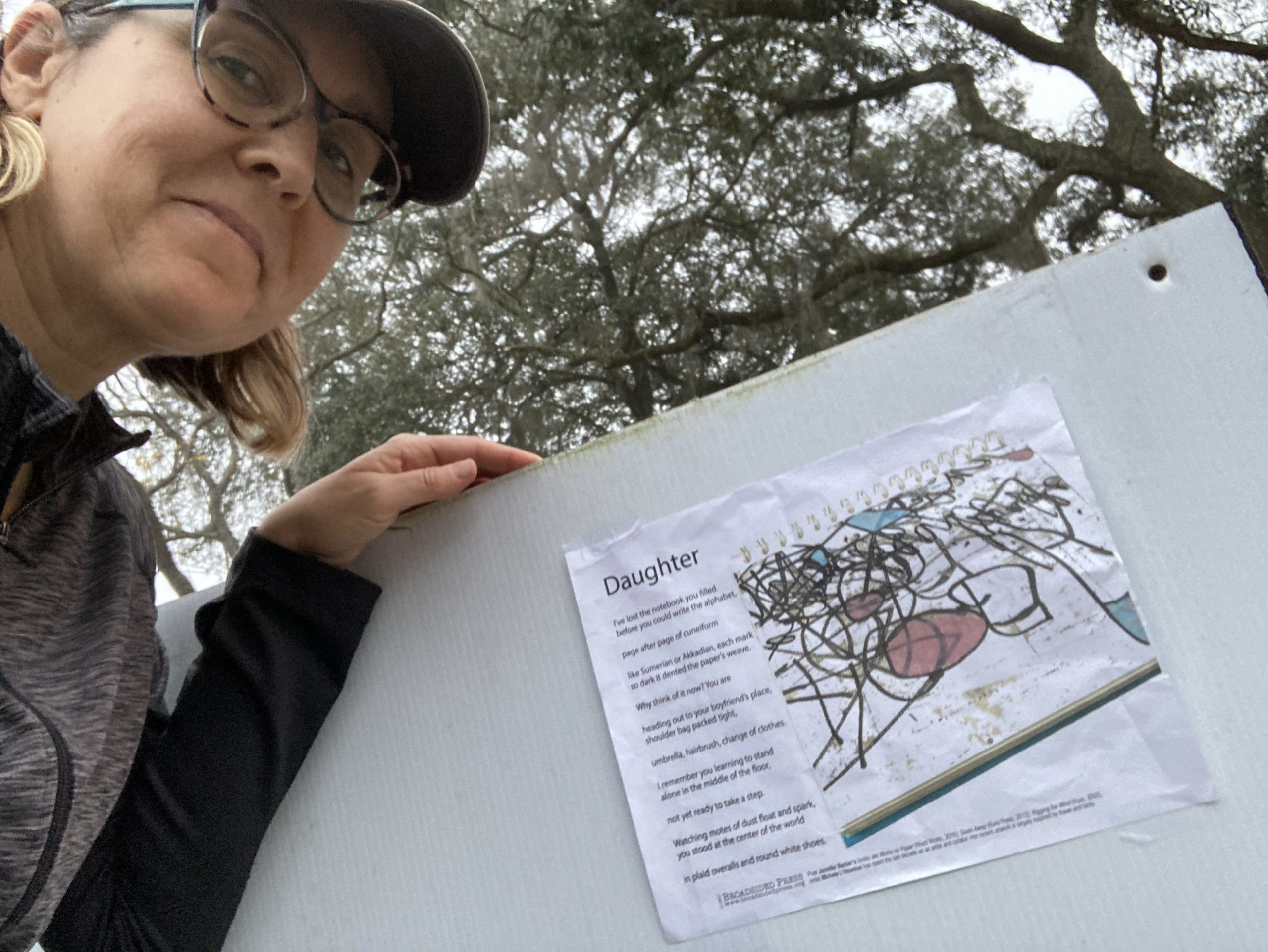Artist Michele L'Hereux stands left of her broadside with trees in the background..