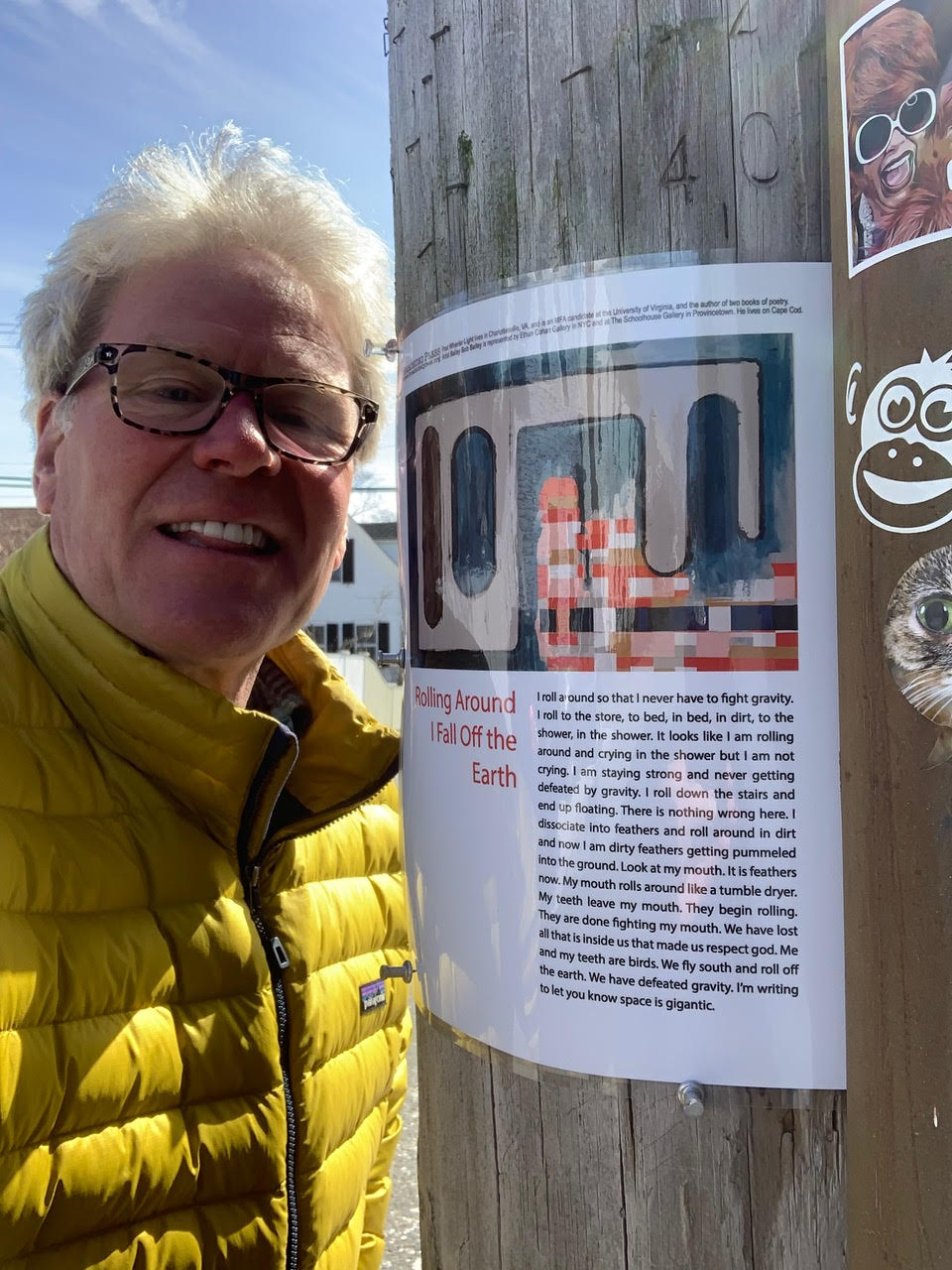 The artist Bailey Bob Bailey standing left to his broadside posted on a telephone pole pasted with quirky stickers on a sunny day.