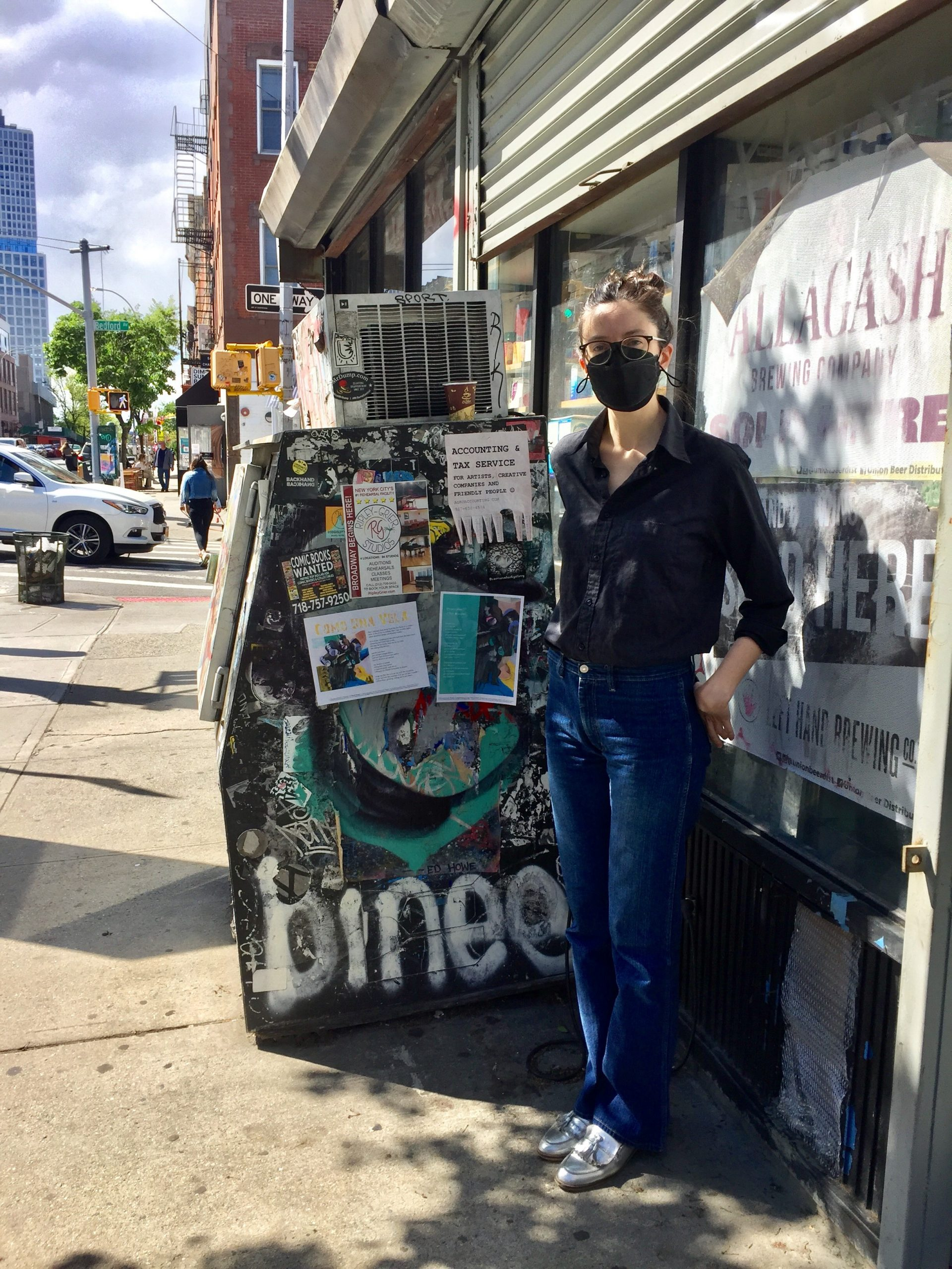 Meghan Keane standing right of her two broadsides pasted on a freezer on a sidewalk..