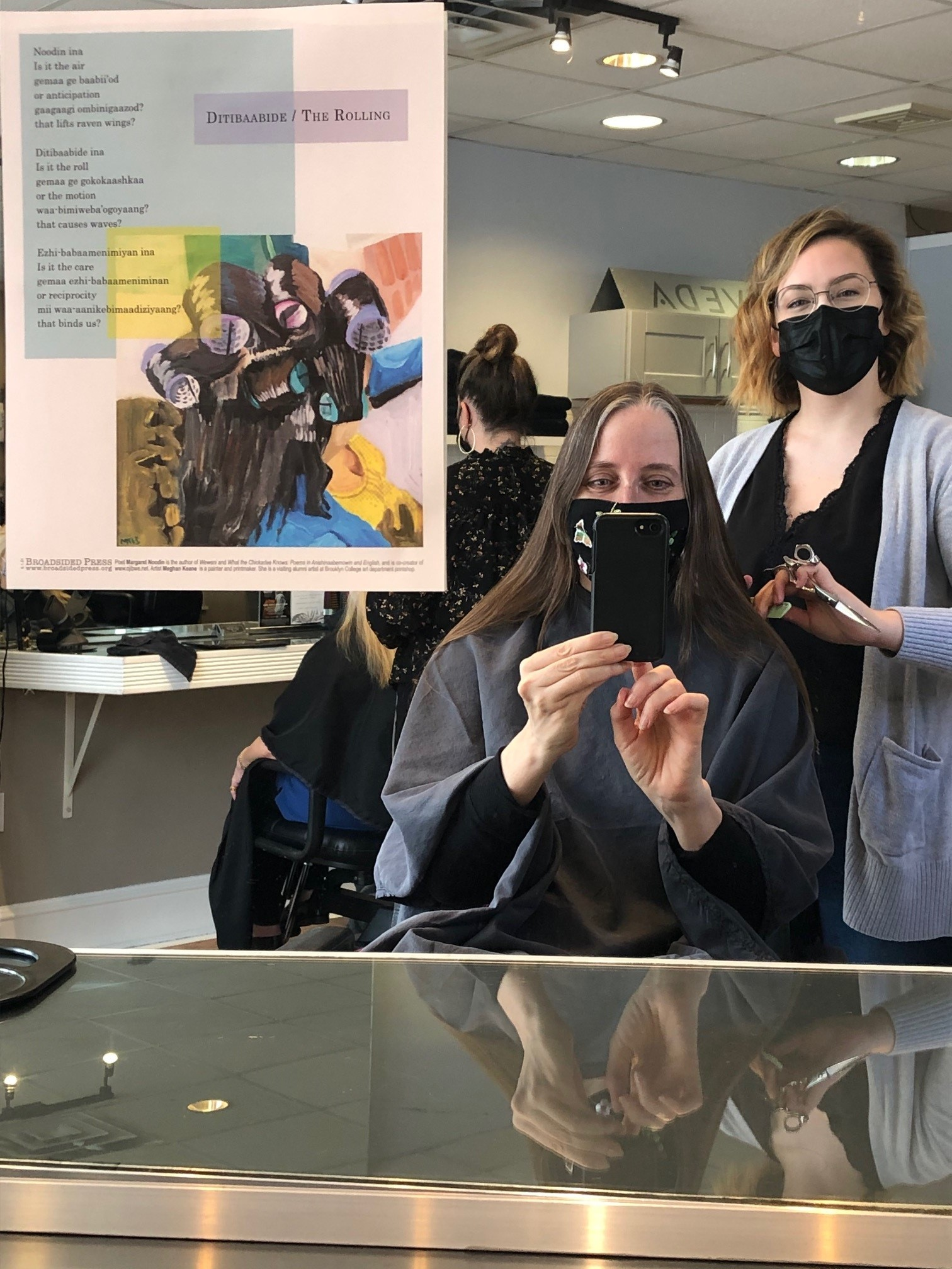 Margaret Noodin and her hair stylist shown in the mirror where her broadside is put.