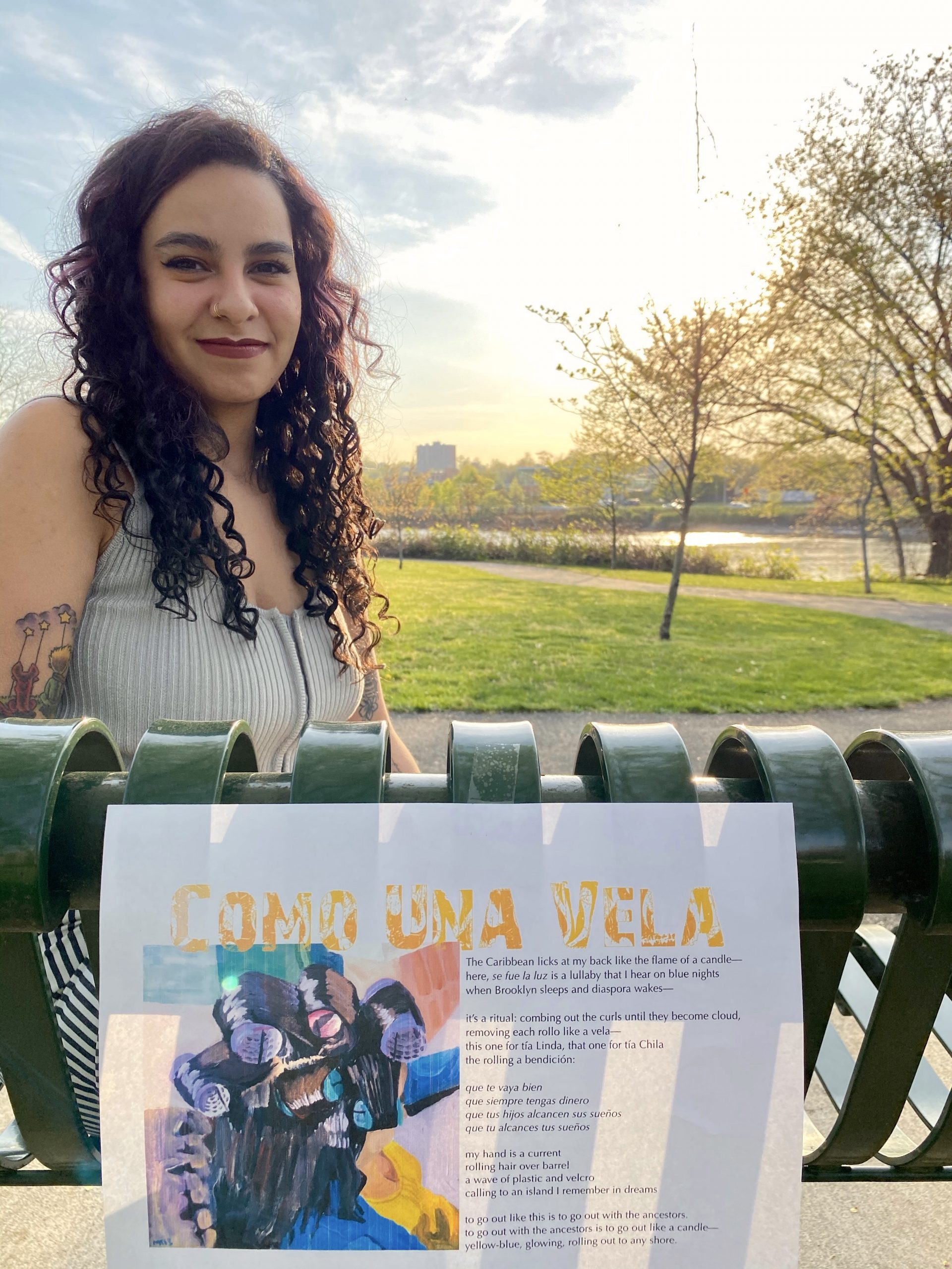 The poet Michelle Moncayo stands left and behind of her broadside with the grassy park in the background.