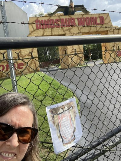 """lower left, artist in sunglasses against a chain link fence topped with barbed wire... behind the fence: """"Dinosaur World"""" on an ugly building with a statue of a pterodactyl above it. Broadside taped to fence."""